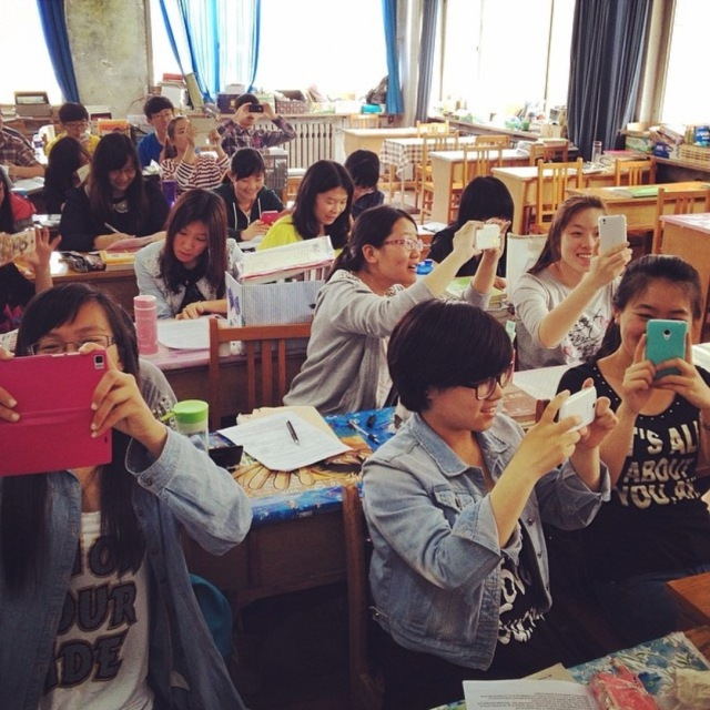 Group of students in a classroom with phones raised.